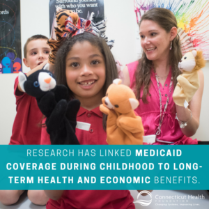 This is a graphic that shows a photo of two children and a teacher playing with puppets, with text over the picture that says research has linked Medicaid coverage during childhood to long-term health and economic benefits.